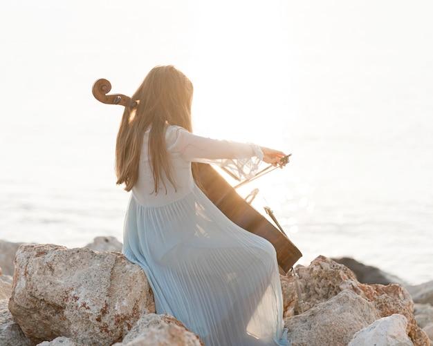 Muzikant speelt cello op rotsen bij de zee