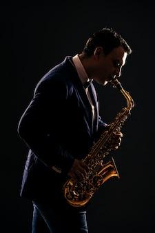 Muzikant speelt jazz op saxofoon. donker