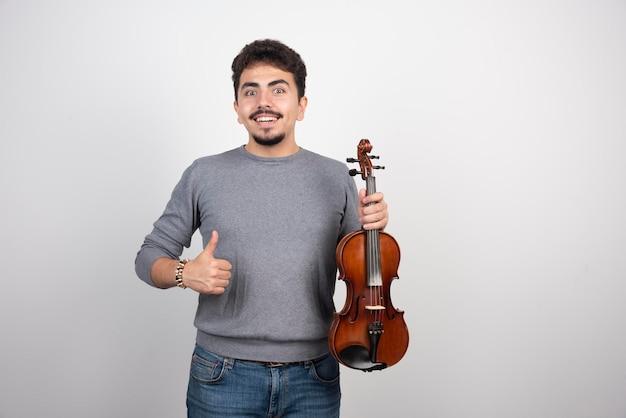 Muzikant speelt viool en ziet er geïnspireerd en positief uit.