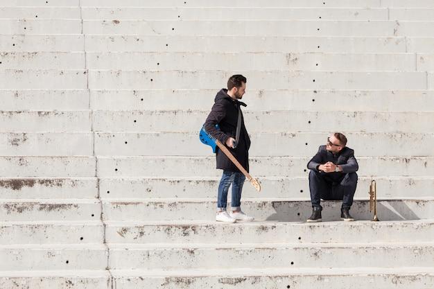 Muzikanten praten op concrete trap
