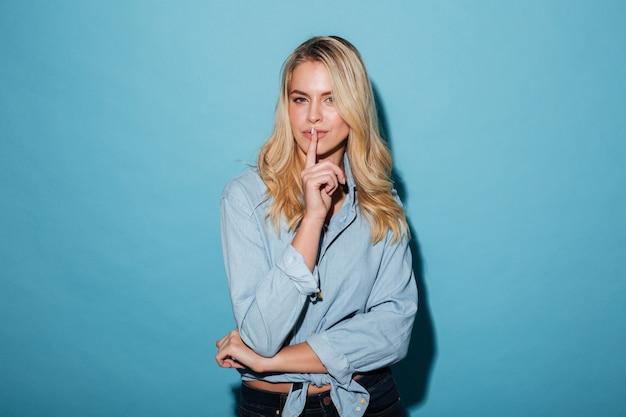 Mysterie blonde vrouw in shirt met stilte gebaar