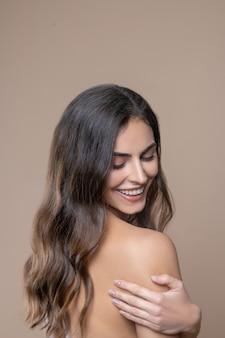 Mysterieus. glimlachende jonge mooie vrouw met lang donker haar met blote schouder en halve draai naar beneden kijkend naar camera