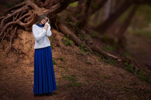 Mysterieus meisje in een mooie blauwe jurk in het bos