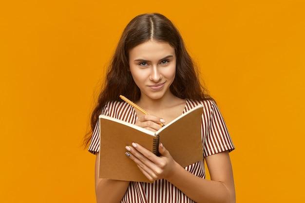 Mysterieuze aantrekkelijke jonge vrouw met lang haar open voorbeeldenboek en pen opschrijven