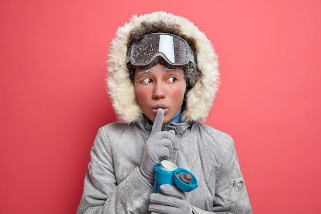 Mysterieuze actieve vrouw maakt stilte gebaar en vertelt geheim wegkijken en probeert op te warmen met warme drank heeft rood ijskoud gezicht gekleed in winter bovenkleding.