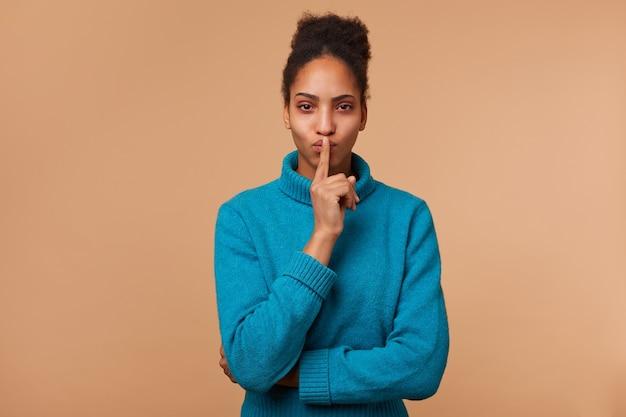 Mysterieuze afro-amerikaanse jongedame, toont een gebaar van stilte, houdt een wijsvinger bij de mond en roept op tot privacy, geheim, blijf stil, kalm. geïsoleerd.