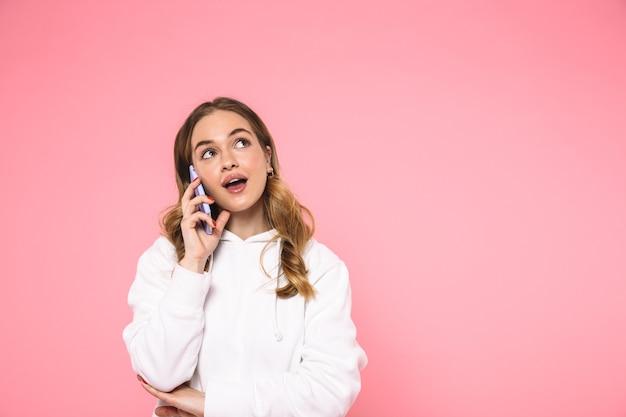Mysterieuze blonde vrouw die in vrijetijdskleding praat met een smartphone en omhoog kijkt over roze muur