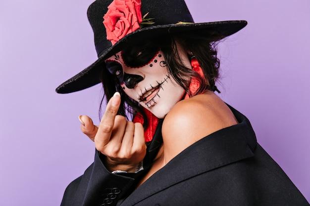 Mysterieuze dame met roos op hoed wenkt vinger om haar te benaderen. close-upportret van aantrekkelijke brunette met rode oorringen.