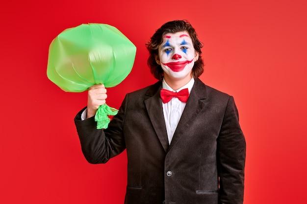 Mysterieuze goochelaar die opgeblazen ballon in handen houdt over rode achtergrond, goochelaar in zwart pak trucs uitvoeren