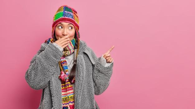 Mysterieuze jonge aziatische vrouw bedekt mond met hand vertelt geheim geeft weg op kopie ruimte draagt grijze bontjas gebreide sjaal en hoed geïsoleerd over roze muur