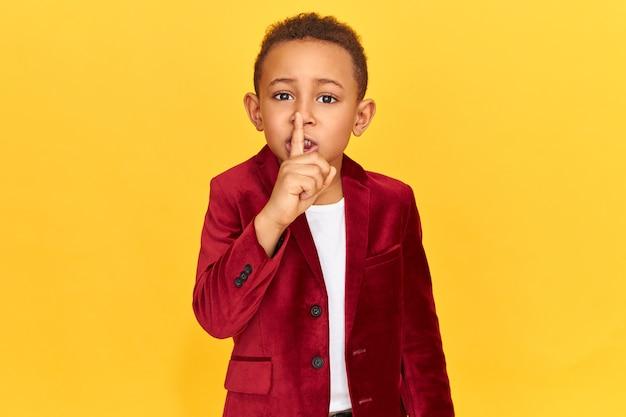 Mysterieuze jongen in stijlvolle kleding zwijgen gebaar maken met wijsvinger op zijn lippen