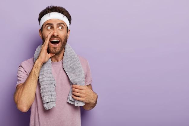 Mysterieuze man houdt van sport, fluistert iets geheims, houdt de handpalm bij de mond, heeft pauze na een vermoeiende training, gekleed in vrijetijdskleding
