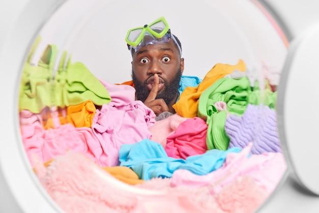 Mysterieuze man maakt stiltegebaar houdt wijsvinger voor lippen vertelt geheim draagt snorkelbril op hoofd verdronken in stapel wasgoed wasmachine voor het wassen van kleding