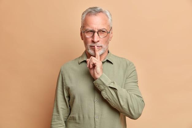 Mysterieuze man met grijs haar maakt zwijggebaar en kijkt met sluwe uitdrukking heeft lastig plan drukt wijsvinger tegen lippen gekleed in formeel overhemd vraagt om te zwijgen