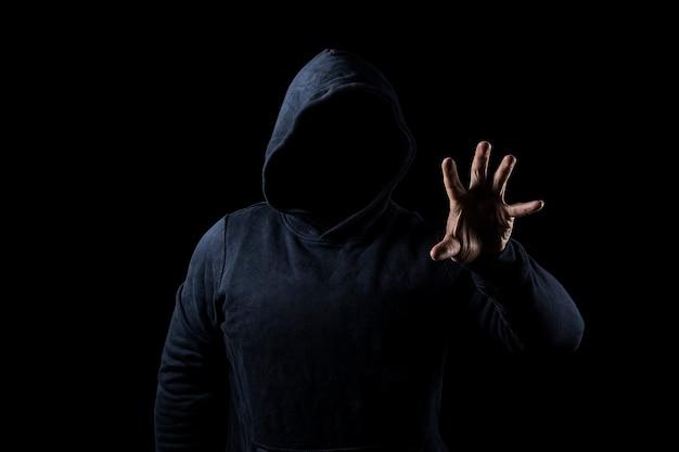 Mysterieuze, onbekende persoon in de kap. gevaar in het donker. anoniem of crimineel concept