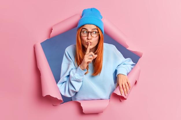 Mysterieuze roodharige vrouw maakt zwijggebaar en vraagt haar geheim niet te vertellen draagt een blauwe hoed en trui verspreidt geruchten kijkt opzij, breekt door papiermuur. lichaamstaal concept. samenzwering.