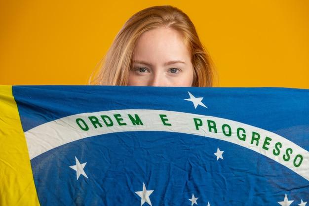 Mysterieuze roodharige vrouwenventilator die een braziliaanse vlag in je gezicht houdt. brazilië kleuren vlag, groen, blauw en geel. verkiezingen, voetbal of politiek.