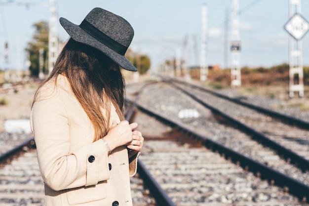 Mysterieuze vrouw in beige trenchcoat en hoed op verlaten spoorlijn.