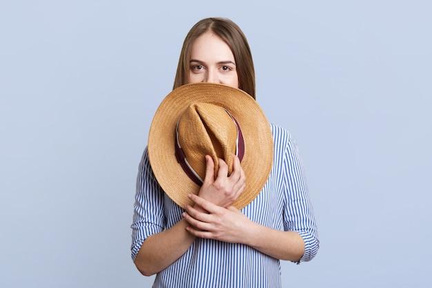 Mysterieuze vrouw in blauwe kleding verbergt onder strooien hoed, poses op blauw. modieuze jonge schattige vrouw toont haar nieuwe aankopen na het winkelen