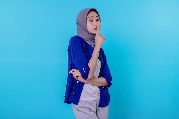 Mysterieuze vrouw maakt stiltegebaar, kijkt weg en vertelt geheim met hijab geïsoleerd over witte muur