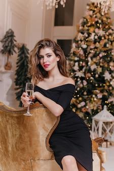 Mysterieuze, vrouwelijke blauwogige dame in elegante zwarte jurk zittend op dure stoel met glas champagne en poseren tegen new year's versierde kerstboom