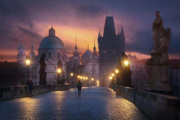 Mystic charles bridge 's nachts met een toerist op de voorgrond