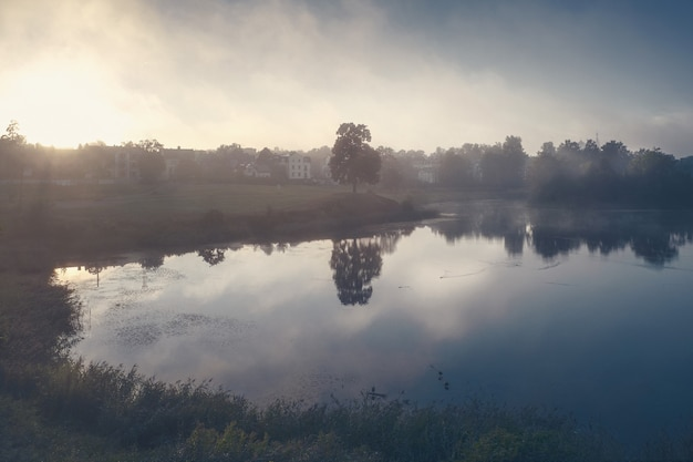 Mystiek de herfstlandschap met mist over het meer in de ochtend