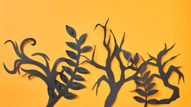 Mystiek patroon van handwerkbladeren en bomen van zwart papier op een oranje achtergrond met ruimte voor tekst. halloween-indeling. plat leggen