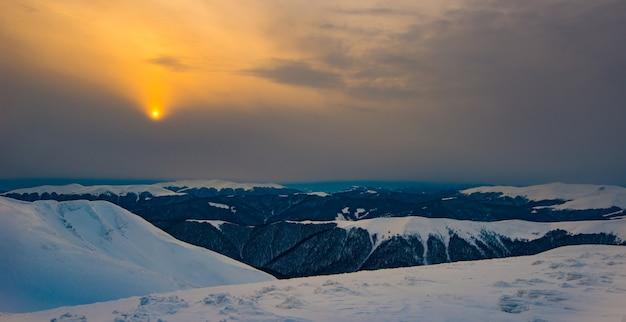 Mystiek uitzicht op de besneeuwde heuvels in een bergdal in de winter tegen de ondergaande gouden zon met een mistige lucht