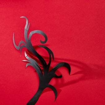 Mystieke compositie van handgeschept kraftpapier een boom uit een patroon van schaduwen op een rode achtergrond met ruimte voor tekst. halloween kaart. plat leggen