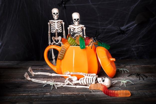 Mystieke halloween-concept. skeletspeelgoed kijkt in een pompoenvormige mok gevuld met feestelijke enge traktaties, geleiwormen en spinnen tegen de achtergrond van spinnenwebben.
