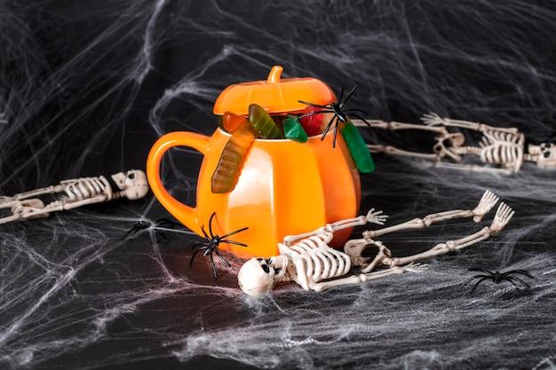 Mystieke halloween-feestconcept. een pompoenvormige mok gevuld met enge lekkernijen, geleiwormen en zwarte spinnen tegen een achtergrond van spinnenwebben en dode skeletten.
