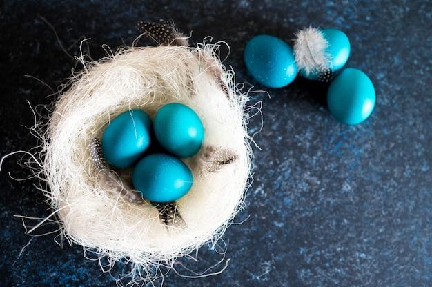 Mystieke kleuren paaseieren met takjes in een decoratief nest op blauw