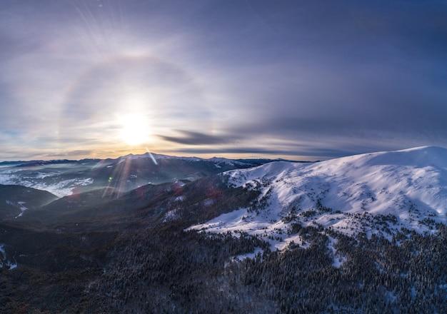 Mystieke luchtfoto van de skipistes van de bergheuvels en bomen bedekt met sneeuw