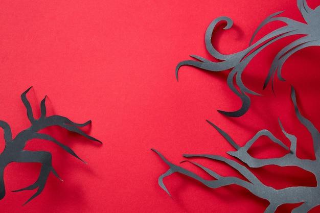 Mystieke patroon van zwarte papieren handwerkbomen op een rode ondergrond met ruimte voor tekst. halloween-indeling. plat leggen