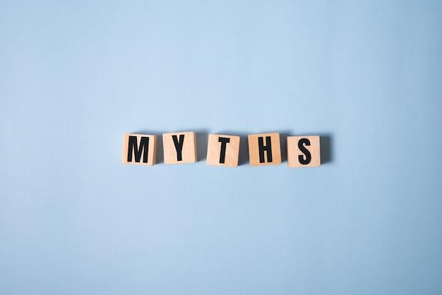 Mythenwoord over houten kubussen. mythen concept op blauw.