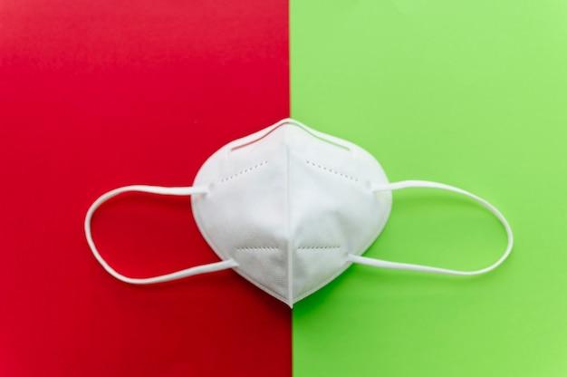 N95 ademhalingsmasker op rode en groene achtergrond met elastische oorbanden. wit. kopieerruimte. bovenaanzicht. aanbevolen bescherming tegen coronavirus