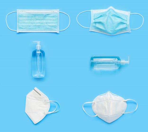 N95 medisch gezichtsmasker met alcohol ontsmettingsmiddel gel handwasfles op blauwe achtergrond covid-19 coronavirus preventie concept minimaal plat lag creatieve stijl