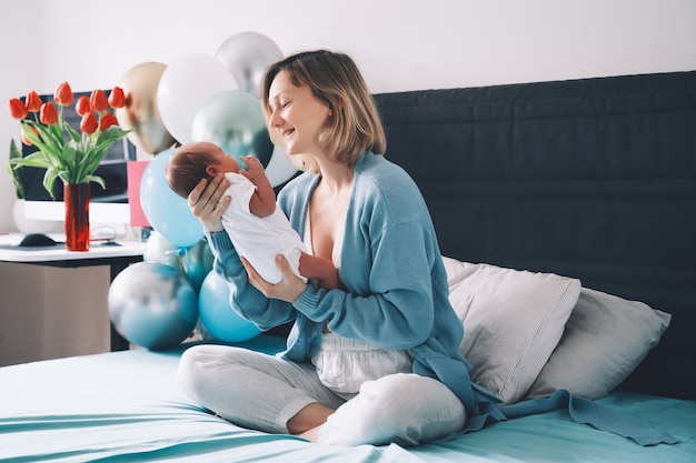 Na de bevalling van de baby moeder en baby thuis houdt moeder pasgeboren in handen moeder en baby samen baby
