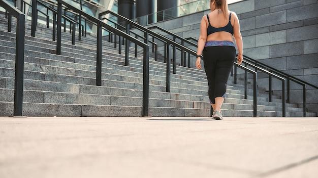 Na de training achteraanzicht van plus size vrouw in sportkleding die naar huis gaat na oefeningen