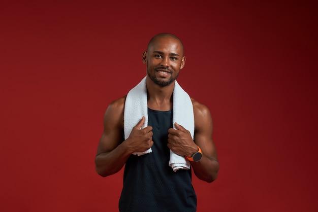 Na de training vrolijke afro-amerikaanse man met handdoek op zijn schouders camera kijken met