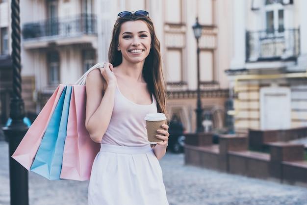Na een dagje shoppen genieten van verse koffie. mooie jonge vrouw die boodschappentassen draagt en een koffiekopje vasthoudt terwijl ze buiten staat