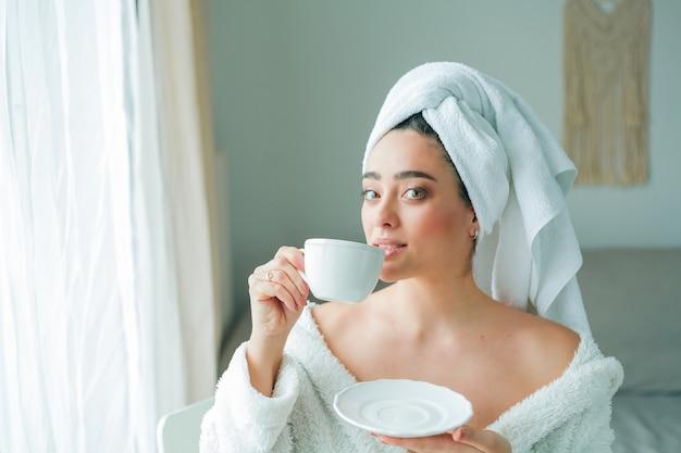 Na een douche drinkt een jonge vrouw in een badjas met een handdoek op haar hoofd koffie en kijkt uit het raam