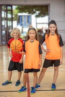 Na een goed spel. kinderen in sportkleding staan met een bal en kijken tevreden
