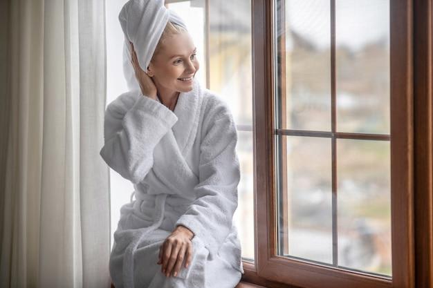Na het bad. een vrouw in een wit gewaad die ontspant na het bad