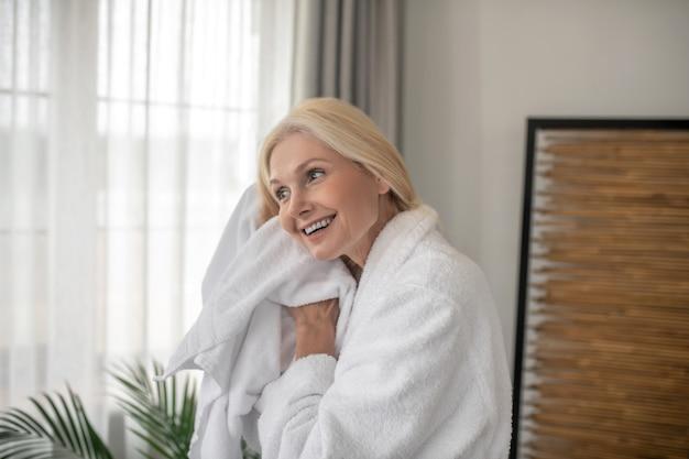 Na het bad. glimlachende blonde vrouw haar haren drogen met een handdoek na het bad
