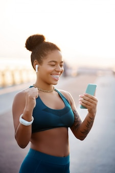 Na het bereiken van het doel. vrouw die sportkleding draagt die gelukkig voelt na het bereiken van haar doel in gewichtsverlies