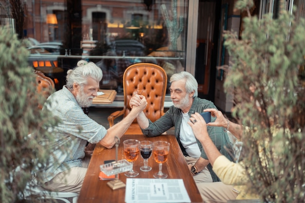 Na het drinken van alcohol. gepensioneerde grijsharige mannen armworstelen na het drinken van alcohol buiten de pub