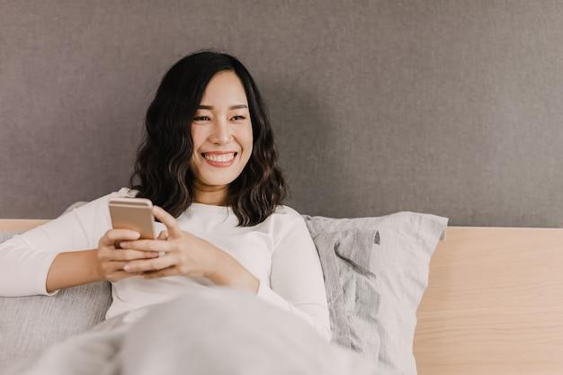 Na het wakker worden lacht de aziatische vrouw op het bed. ze kijkt in de mobiele telefoon en stuurt berichten naar haar vrienden.