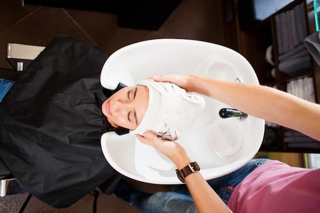 Na het wassen wikkelt de kapper het haar van de cliënt in een handdoek. bovenaanzicht